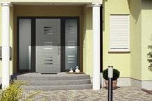 Mit Saeulenornamenten veredelter Eingangsbereich mit glasdurchsetzter Tuer aus Aluminium