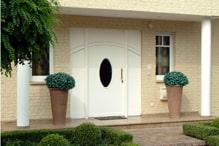 helle Hausfront mit weisser Holztuer mit glasherz